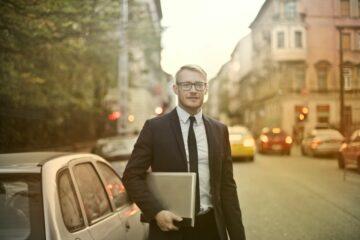 Forretningsmand går på gaden med computer